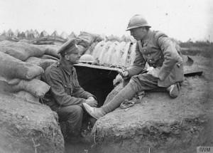 Soldats britannique et français en discussion à l'entrée d'un abri, Bois de Bernafay, 1916, © IWM (Q 79005)